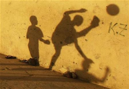 Shadows of children playing soccer are seen on a wall at street in Benguela